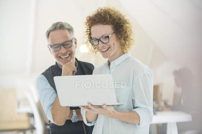 Due impiegati sorridenti che usano il computer portatile — Foto stock