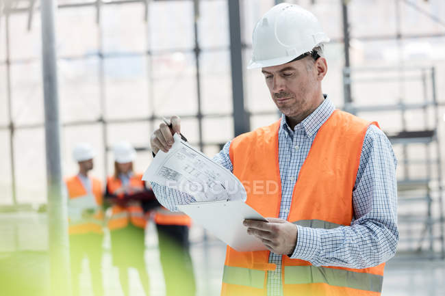Male engineer reviewing blueprints on clipboard at construction site — Stock Photo