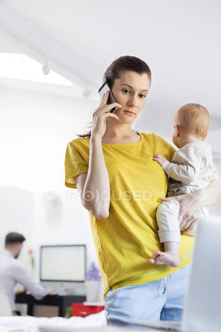 Mother holding baby daughter and talking on cell phone at laptop — Stock Photo