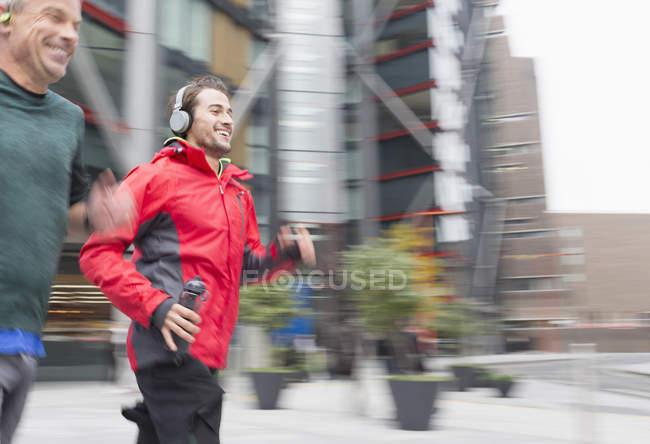Smiling men running, wearing headphones on urban sidewalk — Stock Photo