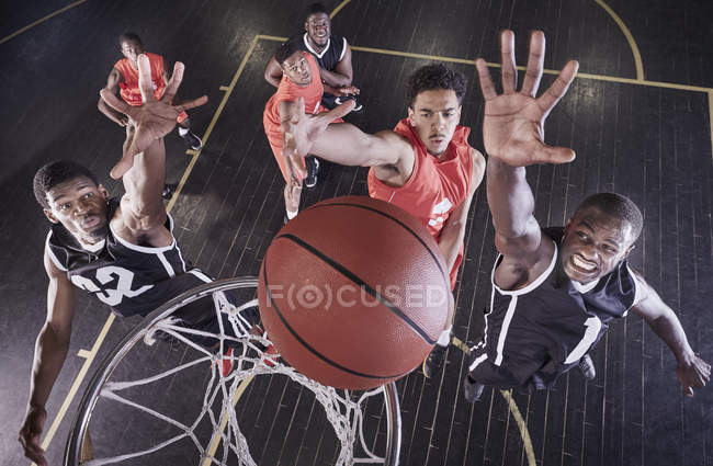 Overhead view young male basketball players jumping to rebound basketball at net on basketball court — стоковое фото