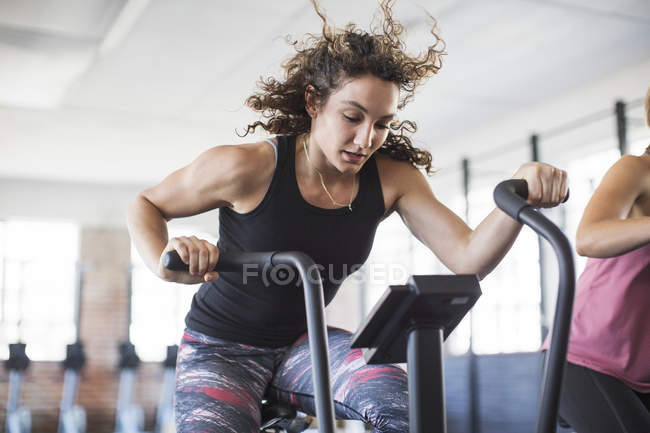 Determined young woman riding elliptical bike in gym — Stock Photo