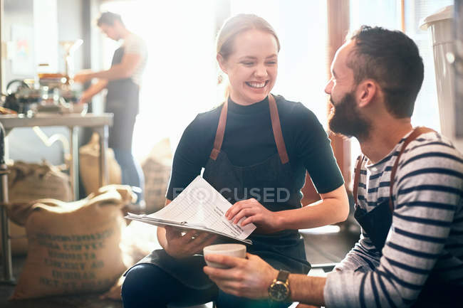 Smiling coffee roasters with clipboard, meeting and tasting coffee — Stock Photo