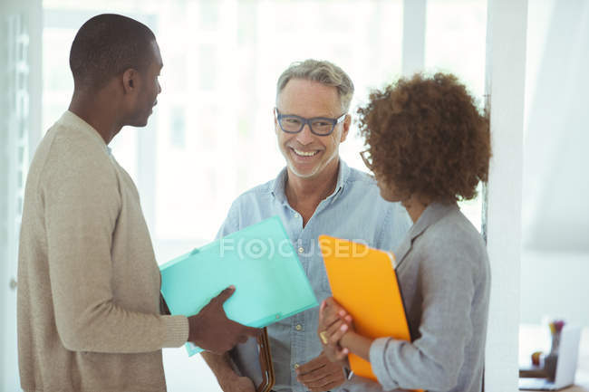 Three office workers talking at office — Stock Photo