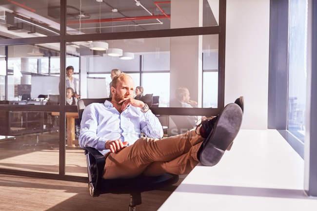 Замислений бізнесмен, сидячи ногами до дивлячись через сонячного вікна в офісі — стокове фото