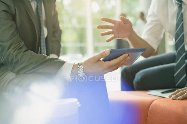 Reunión de empresarios con tableta digital, conversación y gestos - foto de stock