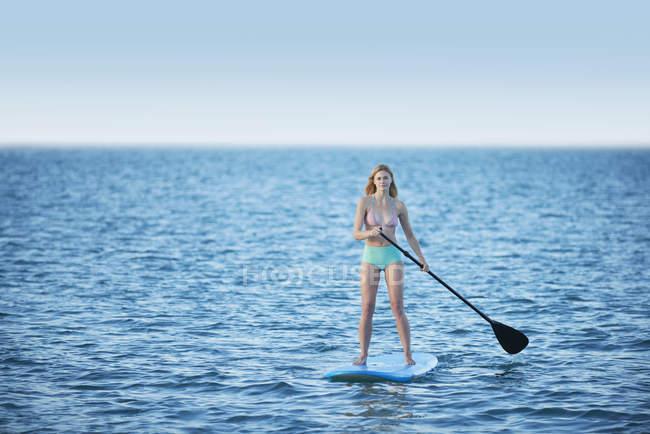 Young woman in bikini paddleboarding on summer ocean — Stock Photo