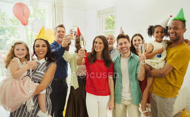 Porträt begeistert multiethnischen-Mehrgenerationen Familie feiern Party mit Champagner und Party Hüte — Stockfoto