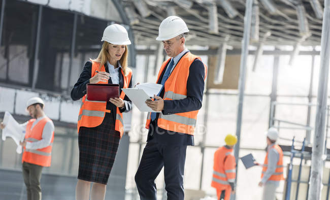 Engineers with clipboards meeting at construction site — Stock Photo