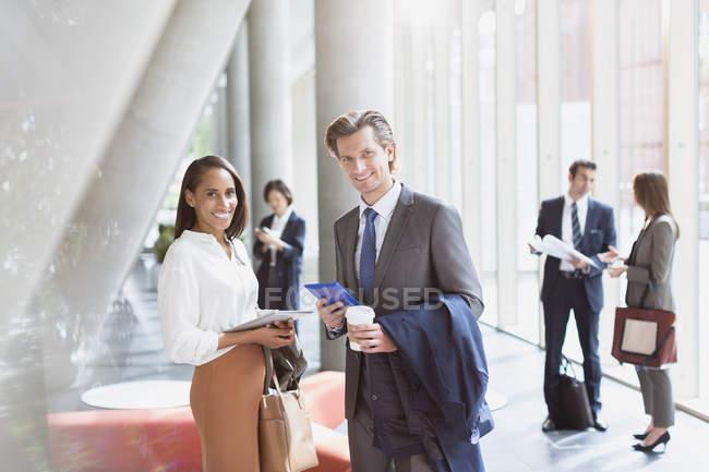 Ritratto uomo d'affari e donna d'affari sorridente nella soleggiata hall dell'ufficio — Foto stock