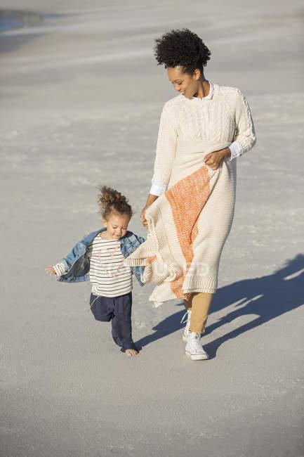 Madre e hija caminando en la playa - foto de stock