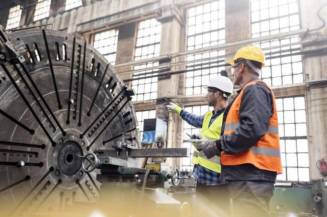 Stahlarbeiter reden in Fabrik miteinander und zeigen auf etwas — Stockfoto