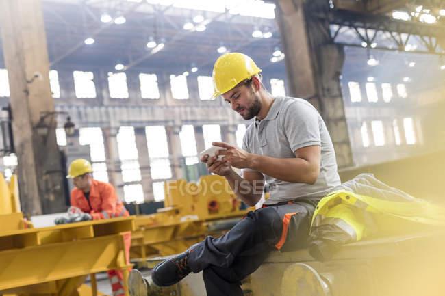 Сталеві працівник текстові повідомлення з мобільного телефону, узявши перерву в заводу — стокове фото
