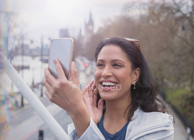 Lächelnd, selbstbewusste Frau, die unter Selfie mit Kamera-Handy auf städtische Brücke — Stockfoto