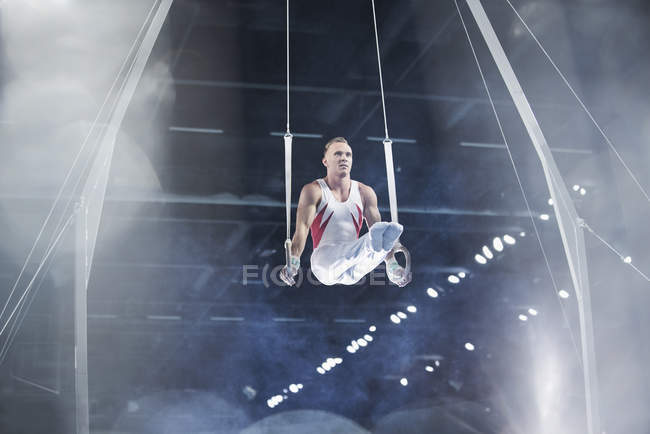 Focused male gymnast performing on gymnastics rings in arena — Stock Photo