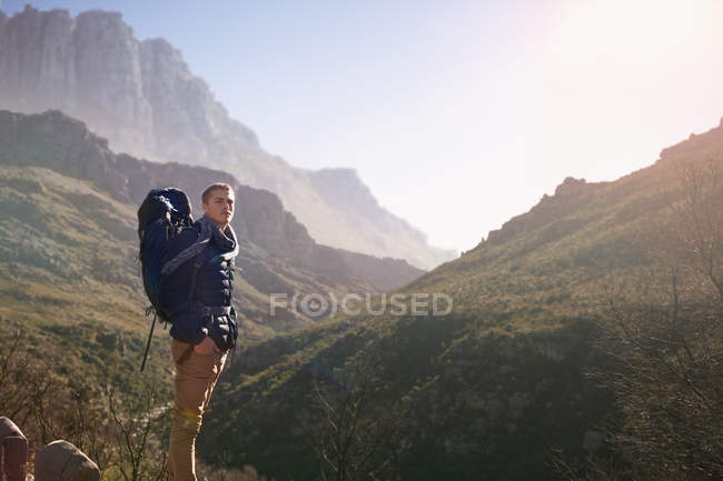 Giovane con lo zaino escursionismo, guardando il sole vista montagna — Foto stock