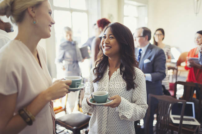 Smiling businesswomen drinking coffee and networking at business conference — Stock Photo