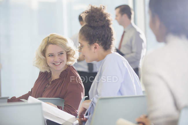 Businesswomen discussing paperwork in conference audience — Stock Photo