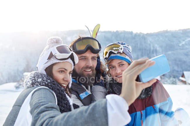 Amici sciatori scattare selfie con fotocamera telefono nel campo innevato — Foto stock