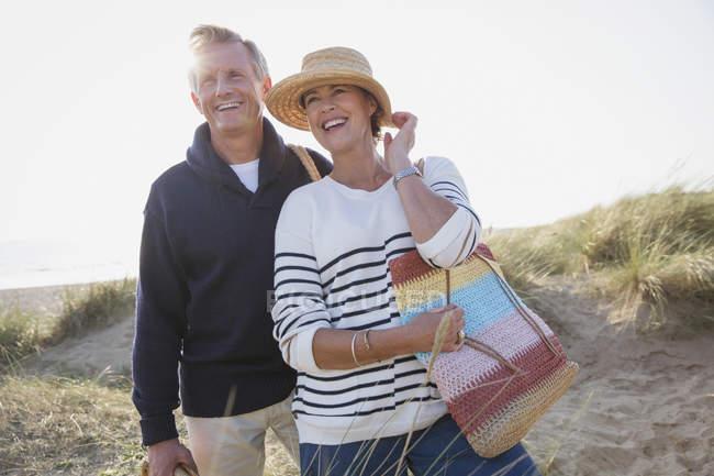 Улыбающаяся зрелая пара на солнечном пляже — стоковое фото
