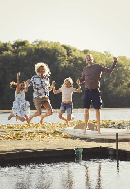Портрет игривая семья прыгает на солнечном озере дока — стоковое фото