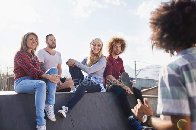 Друзья болтают в солнечном скейт-парке — стоковое фото