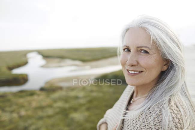 Retrato sonriente mujer mayor en la playa - foto de stock