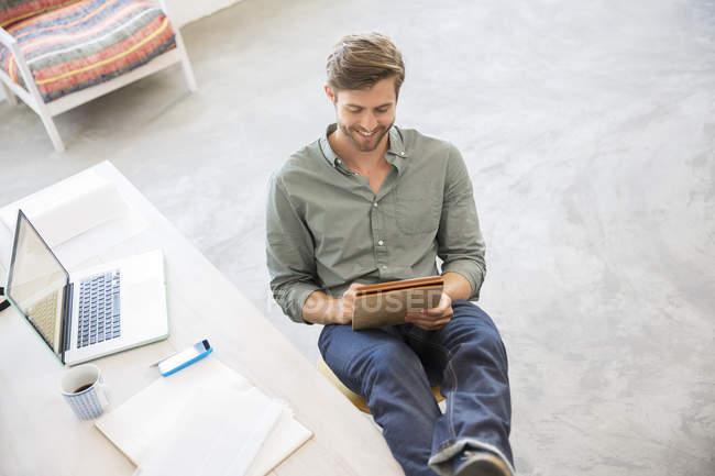 Портрет молодої людини, що сидить з ніг на столі в студії — стокове фото