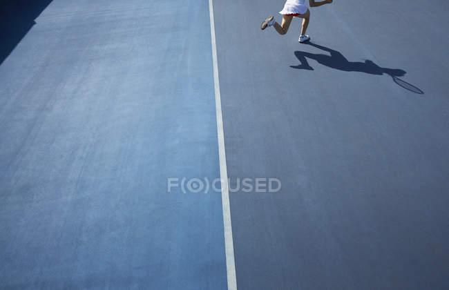 Ombre de joueuse de tennis qui court sur un court de tennis bleu ensoleillé — Photo de stock