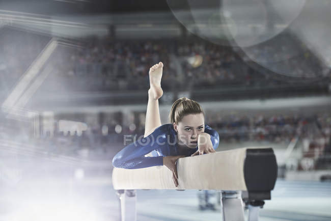 Female gymnast practicing on balance beam in arena — Stock Photo
