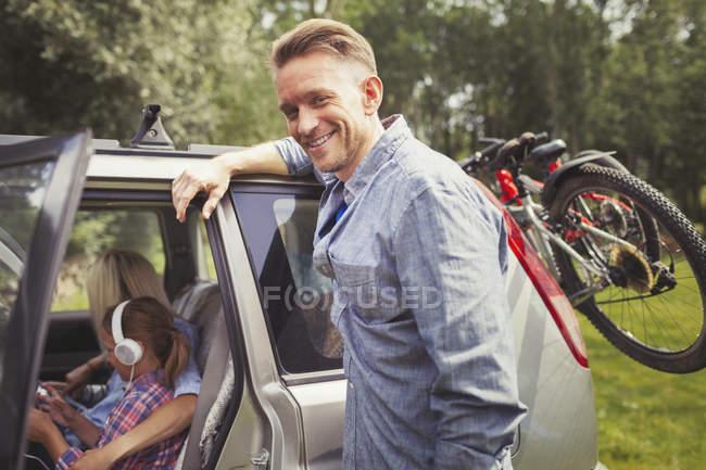 Портрет усміхнений батька, спираючись на автомобіль з гірські велосипеди — стокове фото