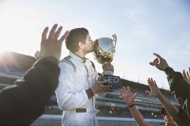 Formula one racing team cheering around driver kissing trophy, celebrating victory — Stock Photo
