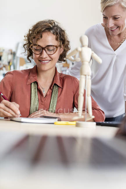 Female design professionals with artist?s figure sketching in office — Stock Photo