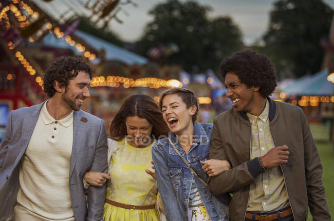 Dos parejas caminando en el parque de atracciones y riendo al atardecer - foto de stock
