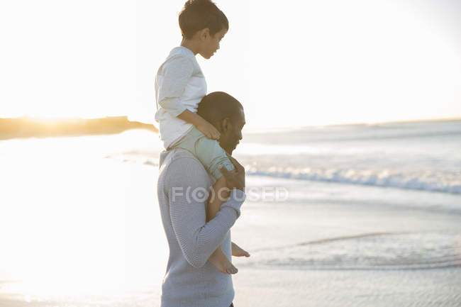 Батько, несучи сина на плечі на пляжі — стокове фото