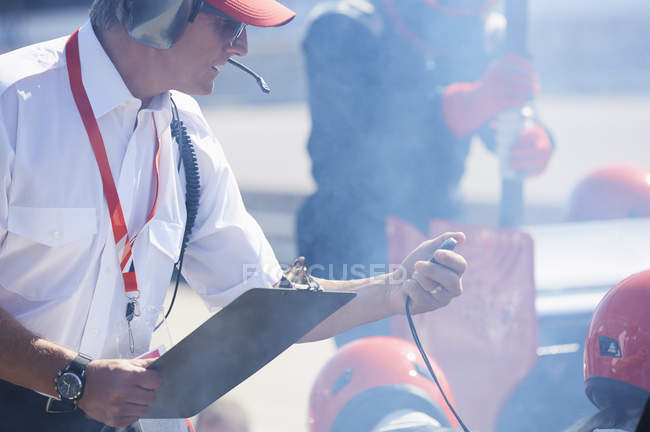 Manager with clipboard and stopwatch timing  formula one pit crew practice session — Stock Photo
