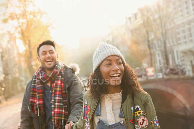 Rire jeune couple marchant sur la rue urbaine d'automne, Amsterdam — Photo de stock