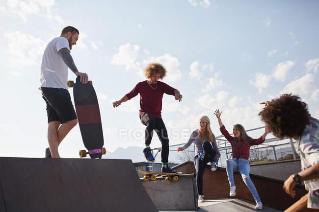 Друзья катаются на скейтборде в парке — стоковое фото