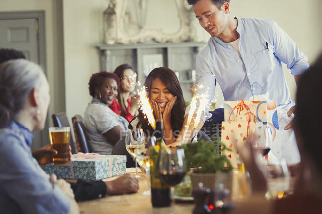 Waiter serving fireworks birthday cake to happy woman at restaurant table — Stock Photo