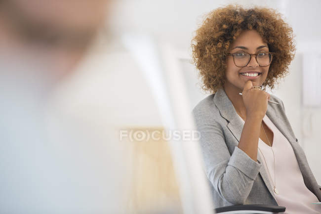 Portrait of woman sitting in office,wearing spectacles and smiling — Stock Photo