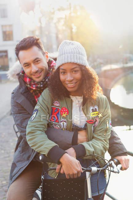 Portrait jeune couple avec vélo serrant le long du canal ensoleillé — Photo de stock