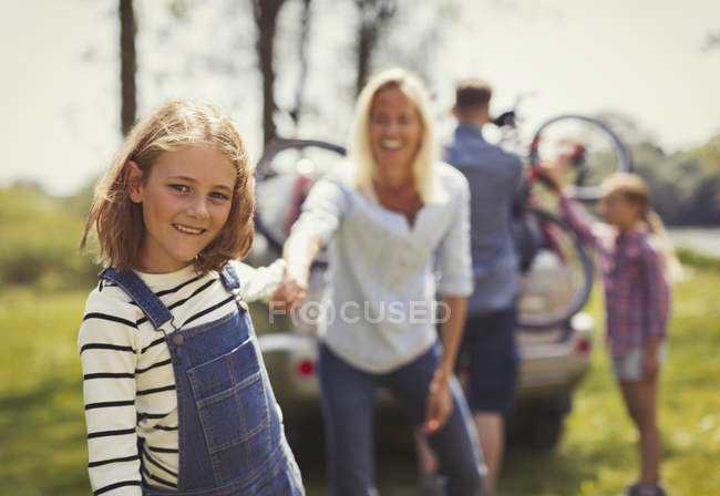 Portrait smiling mother and daughter holding hands outside car — Stock Photo