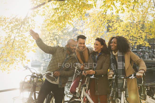 Друзі з велосипедах уздовж каналу Сонячна осінь — стокове фото