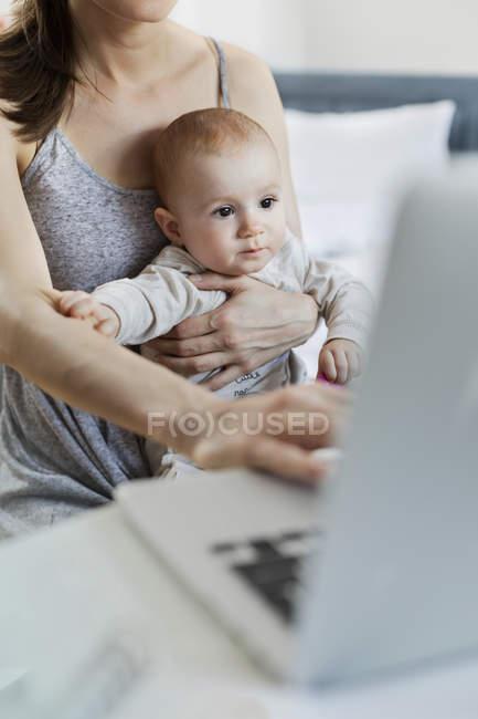 Мать держит на руках маленькую дочь и работает за ноутбуком — стоковое фото