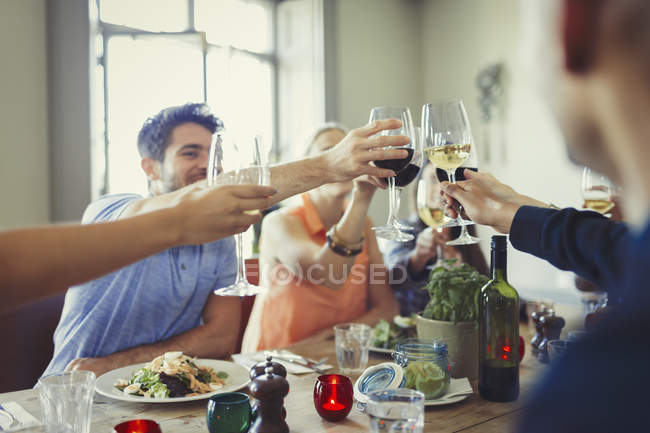 Friends celebrating, toasting wine glasses and dining at restaurant table — Stock Photo