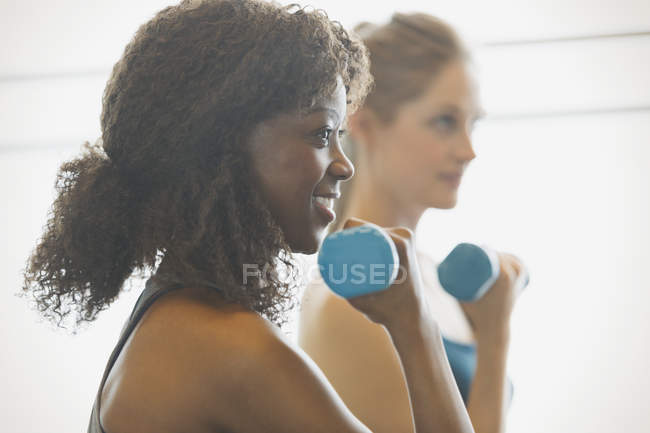 Smiling woman doing biceps curls in exercise class gym studio — Stock Photo