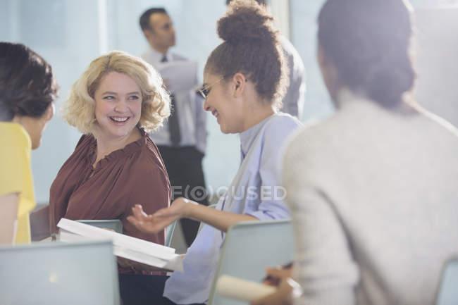 Улыбающиеся деловые женщины обсуждают бумажную работу в аудитории конференции — стоковое фото
