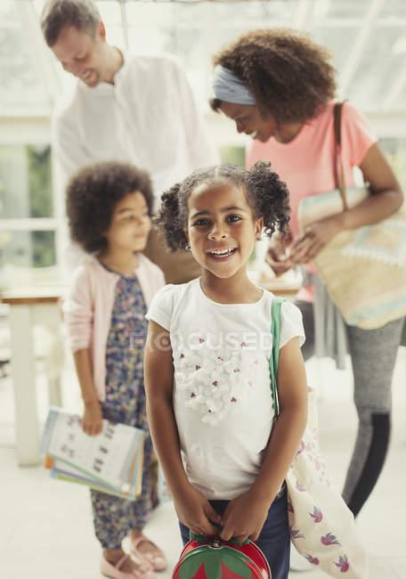 Escolar sonriente retrato listo para salir de casa con la familia - foto de stock