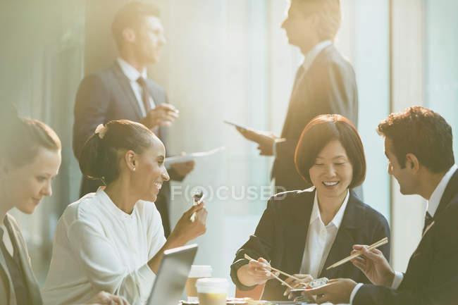 Des hommes d'affaires souriants déjeunent avec des baguettes dans la salle de conférence — Photo de stock