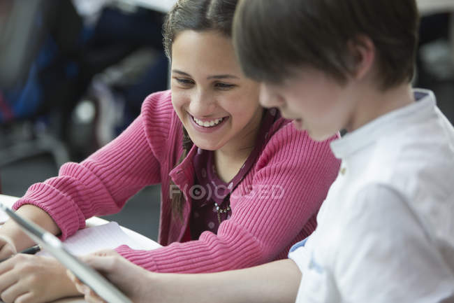 Studenti sorridenti che usano tablet digitale in classe — Foto stock